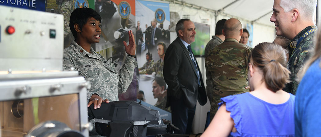 A military member in a booth demonstrating a piece of equipment for attendees of the Lab Day.
